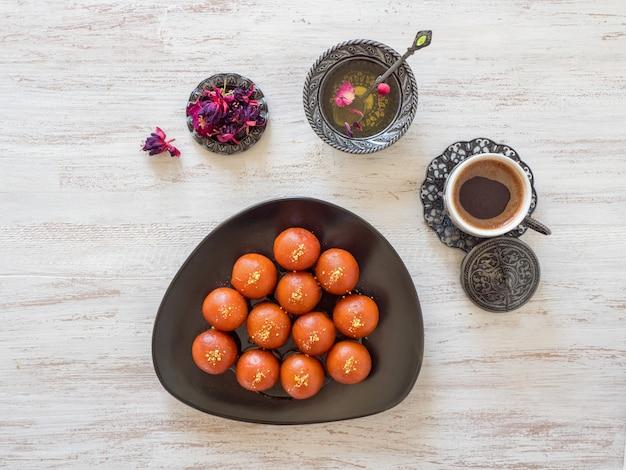 Gulab jamun - dolci indiani tradizionali su una tavola di legno bianca
