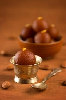 Gulab jamun in ciotola e ciotola antica in rame con cucchiaio. dessert indiano o piatto dolce.