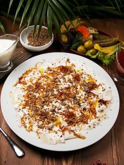 Guru azero khingal - pasta caucasica con carne tritata fritta e cipolla.