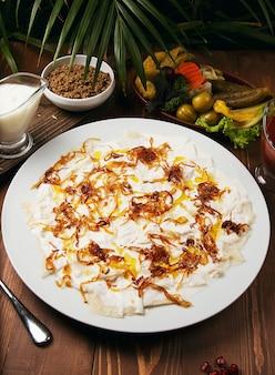 Guru dell'azerbaigian khingal - pasta caucasica con carne e cipolla fritta.