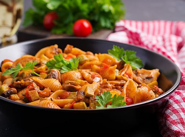 Gusci di pasta italiana con funghi, zucchine e salsa di pomodoro