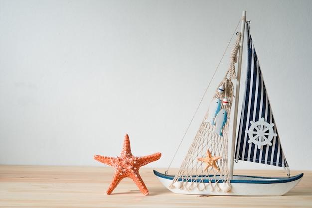 Gusci di repliche, simulatori di yacht, poggiati su un concetto di treppiede in legno.