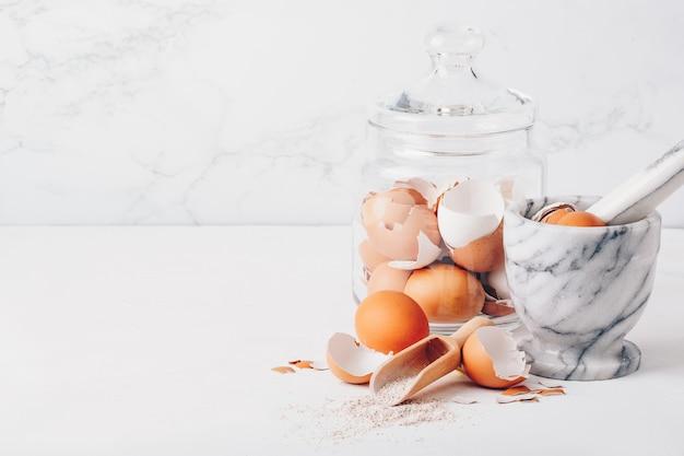 Guscio d'uovo macinato, calcio fatto in casa. mortaio di marmo, uova, conchiglie, calcio
