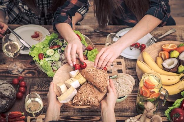 Gustando la cena con i miei amici. vista dall'alto di un gruppo di persone che cenano insieme, seduti a un tavolo in legno rustico, il concetto di festa e sano cibo cucinato in casa