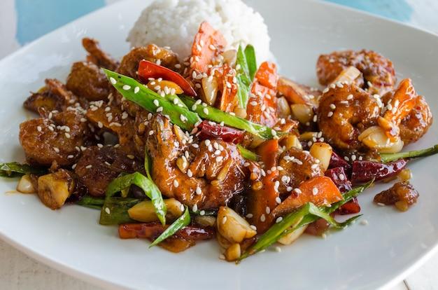 Gusto dell'asia e dello sri lanka - piatto di riso e gamberi in pastella, salsa dolce, decorato con semi di sesamo su un piatto bianco.