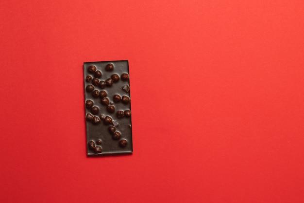 Gustosa barretta di cioccolato fondente su uno sfondo rosso in stile piatto con posto per il testo