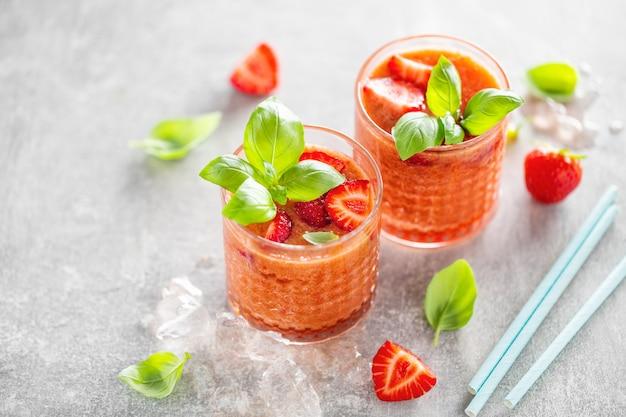 Gustosa bevanda appena fatta con stawberry e basilico servito in bicchieri sul tavolo di cemento.