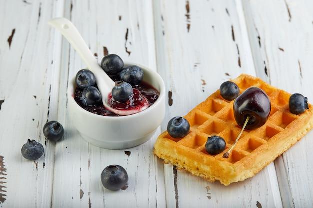 Gustosa colazione cialde belghe con mirtilli panna montati e marmellata su un bianco di legno