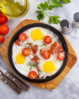 Gustosa colazione con uova fritte, pancetta e verdure su una padella