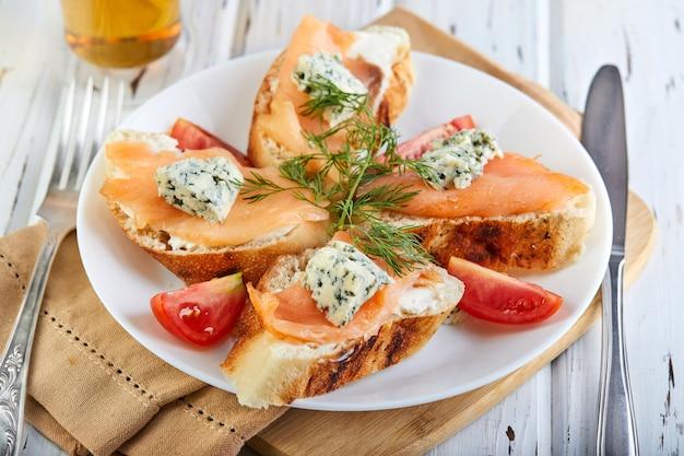 Gustosa colazione panini con i salmoni e formaggio e pomodori ciliegia su un bianco di legno