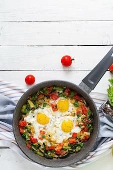 Gustosa colazione uova fritte con verdure. shakshuka. vista dall'alto. disteso
