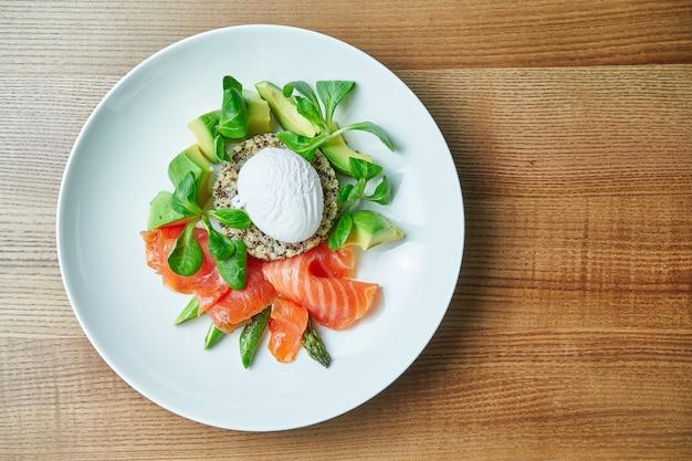Gustosa e salutare colazione continentale - quinoa con uova alla benedict, spinaci, avocado, salmone salato e asparagi in ciotola bianca. tavolo di legno