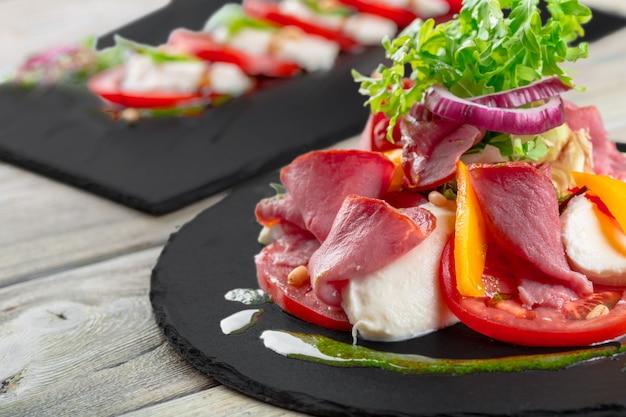 Gustosa insalata di cachi con rucola, prosciutto di parma, olio d'oliva ed erbe aromatiche
