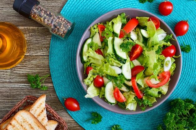 Gustosa insalata dietetica vitaminica con cetrioli freschi, pomodori, verdure. insalata di verdure biologiche. vista dall'alto, piatto.