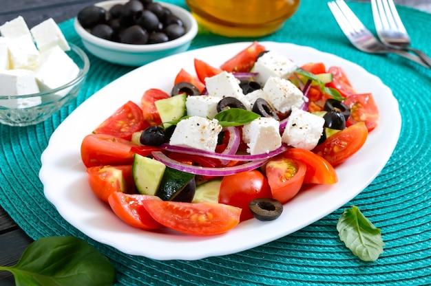 Gustosa insalata vegetariana di pomodoro, cetriolo, cipolla rossa e olive nere