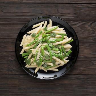Gustosa pasta con parmigiano e baccelli verdi su un piatto nero. cibo sano.
