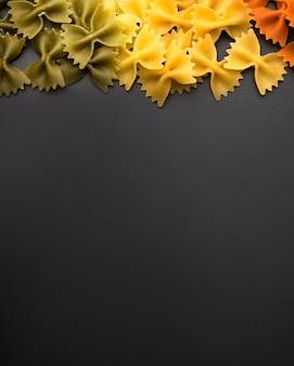Gustosa pasta di farfalle su superficie nera con copia spazio per il testo