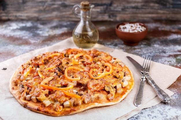 Gustosa pizza con pollo, peperoni e formaggio su legno
