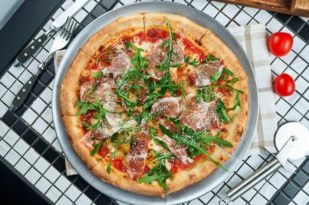 Gustosa pizza con prosciutto di parma, rucola e parmigiano su un tavolo bianco. cucina tradizionale italiana. piatti deliziosi piatti laici. vista dall'alto