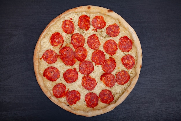 Gustosa pizza con vari ingredienti aromatizzati al buio