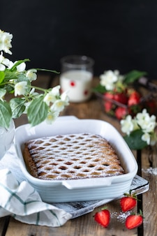 Gustosa torta di frutti di bosco con fragole sul tavolo di legno. verticale