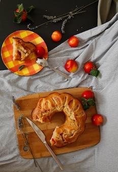 Gustosa torta di prugne sul vassoio di legno e prugne rosse sul tovagliolo spogliato sul tavolo nero con fiori