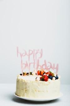 Gustosa torta fresca con frutti di bosco e titolo di buon compleanno sul piatto