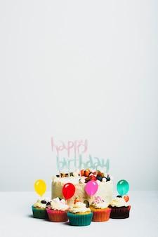 Gustosa torta fresca con frutti di bosco e titolo di buon compleanno vicino set di muffin