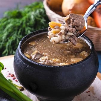 Gustosa zuppa di carne e funghi in una pentola. avvicinamento