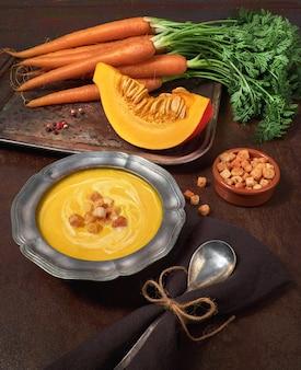 Gustosa zuppa di zucca e carote servita con crostini e semi di zucca in una ciotola di peltro di metallo
