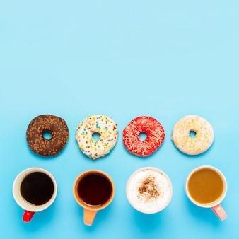Gustose ciambelle e tazze con bevande calde, caffè, cappuccino, tè su una superficie blu. concetto di dolci, prodotti da forno, pasticceria, caffetteria, meeting, amici, squadra amichevole. piazza. vista piana, vista dall'alto