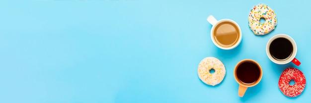 Gustose ciambelle e tazze con bevande calde, caffè, cappuccino, tè su una superficie blu. concetto di dolci, prodotti da forno, pasticceria, caffetteria, meeting, amici, squadra amichevole. vista piana, vista dall'alto