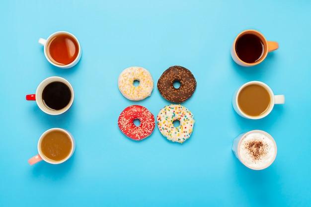 Gustose ciambelle e tazze con bevande calde su una superficie blu. concetto di dolci, prodotti da forno, pasticceria, caffetteria, amici, squadra amichevole. vista piana, vista dall'alto