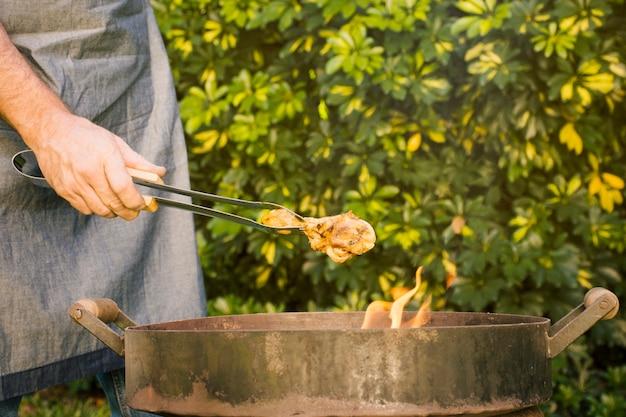 Gustose grigliate di carne in pinze metalliche sulla griglia fuoco in mano