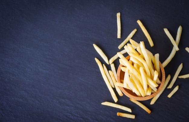 Gustose patatine fritte per cibi o snack deliziosi menu italiani con ingredienti fatti in casa. patate fritte fresche sulla ciotola e sulla banda nera di legno