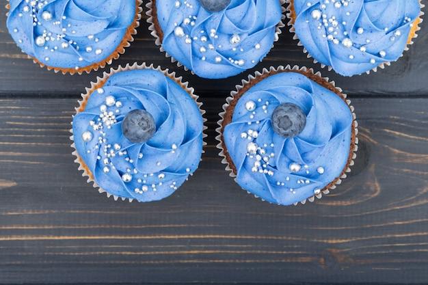 Gustosi cupcakes su un tavolo di legno bianco