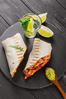 Gustosi fast food: burritos messicani con salsa guacamole su fondo di legno nero