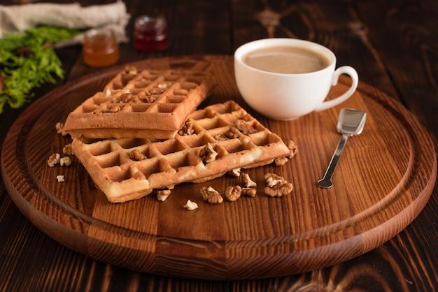 Gustosi freschi wafer di vienna, marmellata e tazza di caffè su uno sfondo di legno scuro