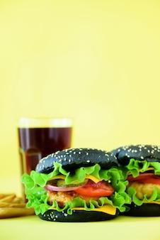 Gustosi hamburger o hamburger neri serviti con patatine fritte. fast food a colazione, pranzo.