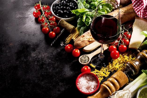 Gustosi ingredienti freschi appetitosi di cibo italiano su sfondo scuro.