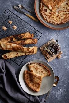 Gustosi pancake fatti in casa con marmellata di bacche servita sul tavolo di pietra grigia
