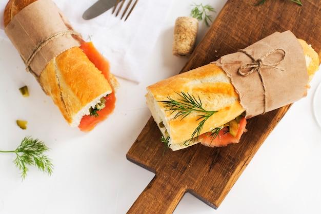 Gustosi panini con salmone affumicato sul tavolo bianco