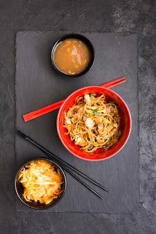 Gustosissimi spaghetti di pollo con zuppa e insalata su pietra ardesia nera
