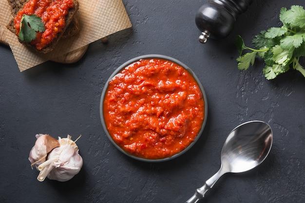 Gustoso ajvar. salsa di verdure o caviale di peperone dolce rosso al forno sul nero. cucina balcanica.