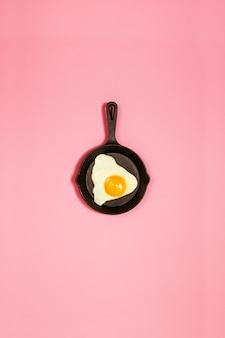 Gustoso bel cibo uovo fritto in padella su sfondo rosa di moda. concetto minimalistico. vista dall'alto.