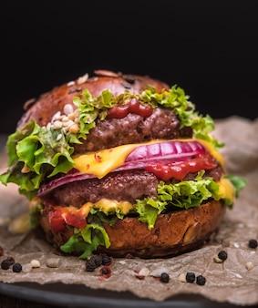 Gustoso cheeseburger alla griglia doppio hamburger con pepe e insalata