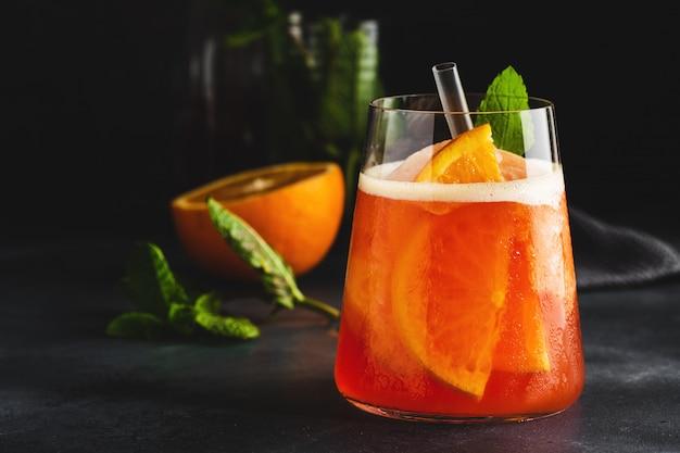 Gustoso cocktail estivo rinfrescante dolce appena fatto con arance e menta servito in bicchiere. avvicinamento