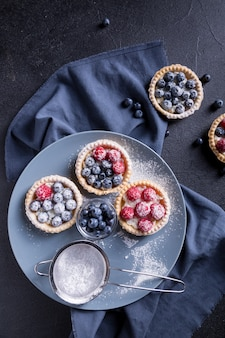 Gustoso dessert con mirtilli freschi e lamponi su un grande piatto grigio. sfondo nero.