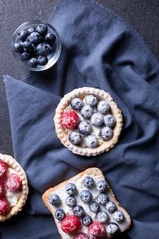Gustoso dessert con mirtilli freschi e lamponi su uno sfondo nero.