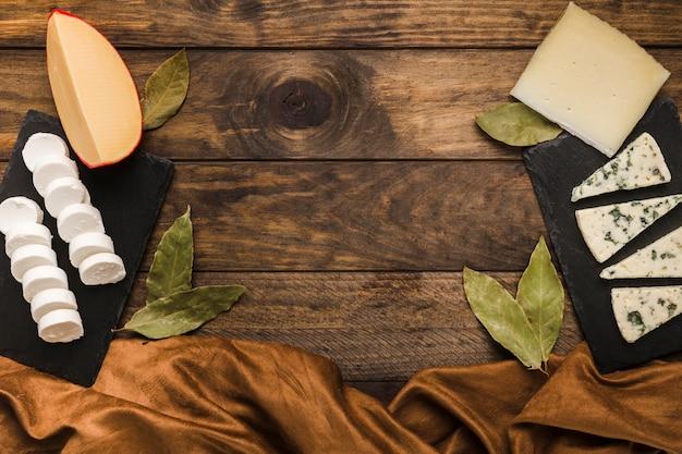 Gustoso formaggio su roccia nera di ardesia con foglie di alloro e tessuto di seta sulla superficie in legno